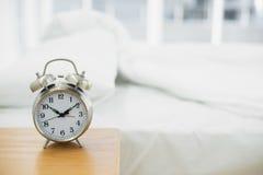Retro- Wecker, der auf einem Nachttisch steht Stockbilder
