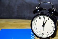 Retro- Wecker des Konzeptweinlesehintergrundschwarzen auf 13 00 P.M. oder 01 00 morgens und blaues Buch stockfotos
