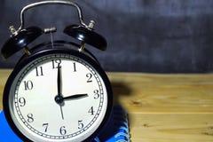 Retro- Wecker des Konzeptweinlesehintergrundschwarzen auf 15 00 P.M. oder 03 00 morgens und blaues Buch stockfotografie