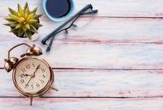Retro- Wecker, Gläser, Tasse Kaffee und Blume auf einem hölzernen t Lizenzfreies Stockbild