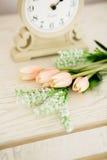 Retro- Wecker mit Blumen auf hölzernem rostigem Hintergrund Stockfoto