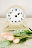 Retro- Wecker mit Blumen auf hölzernem rostigem Hintergrund Lizenzfreie Stockbilder