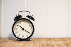 Retro- Wecker mit 10 O-` Uhr und Menuett zwanzig, auf Holztisch- und Weißhintergrund mit Kopienraum Stockbild