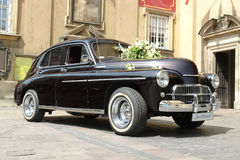 Retro wedding car. Black retro wedding car waiting in front of the church for the newly married couple Royalty Free Stock Photos
