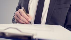 Retro- Weinleseartbild eines Geschäftsmannes, der einen Vertrag unterzeichnet Stockfotos