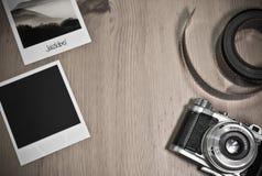 Retro- Weinlesephotographiekonzept von zwei sofortigen Fotorahmenkarten auf hölzernem Hintergrund mit altem Kamera- und Filmstrei Stockfotos