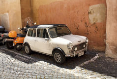 Retro, white, little, old car parked next to motorcycle. On one of the streets in Trastevere in Rome Stock Photography