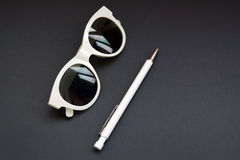 Retro white sunglasses and pen on black table. White  sunglasses and pen Isolated on black background with Stock Photos