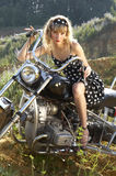 Retro woman on a bike. Woman in an retro dress on a motorbike Royalty Free Stock Photo