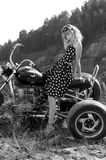 Retro woman on a bike. Woman in an retro dress on a motorbike Stock Photo
