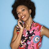 Retro woman on cellphone. Woman with afro wearing vintage print fabric smiling holding cellphone Stock Photo