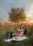 Retro woman in field. Retro woman sitting with a book and pencil in her hand and an accordion at her feet on a large white sheet, in a field of tall grass stock photos