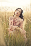 Retro woman in field. Portrait of a young woman dressed in retro clothes, sitting in a field of tall grass Stock Photography