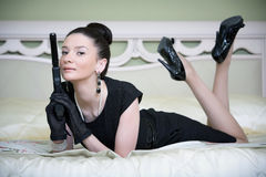 Retro woman with a gun in a hotel woman. Posing stock image