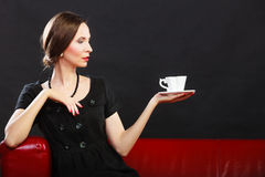 Retro woman holds tea cup sitting on sofa Stock Images