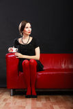 Retro woman holds tea cup sitting on sofa Royalty Free Stock Images