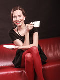 Retro woman holds tea cup sitting on sofa Stock Image