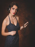Retro woman listening to music from phone Stock Image