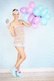 Retro woman with lollipop and balloons. A picture of a retro woman posing with a lollipop and balloons over white and blue dotted background royalty free stock photo