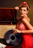Retro woman with music vinyl record. Girl pin-up style wearing red dress. Royalty Free Stock Photos