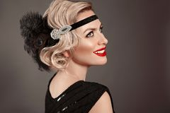 Retro woman portrait. Blonde wavy hairstyle. Hollywood red lips makeup. Curly hair style. Beautiful elegant female wears in. Vintage dress isolated on dark royalty free stock images