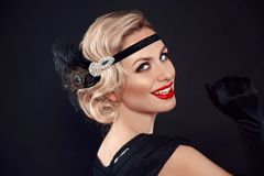 Retro woman portrait. Blonde wavy hairstyle. Hollywood red lips makeup. Curly hair style. Beautiful elegant female wears in. Vintage dress isolated on black royalty free stock images