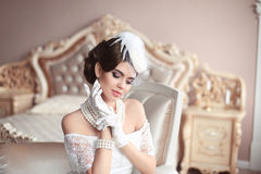 Retro woman portrait. Elegant brunette lady with hairstyle, pear. Ls jewelry set wears in hat and lace gloves posing on modern armchair in luxury bedroom Stock Images