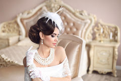 Retro woman portrait. Elegant brunette lady with hairstyle, pear. Ls jewelry set wears in hat and lace gloves posing on modern armchair in luxury bedroom Royalty Free Stock Image