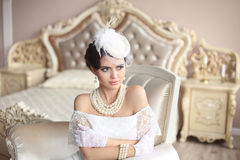 Retro woman portrait. Elegant brunette lady in hat with hairstyl. E, pearls jewelry set. Pretty female posing on modern armchair in luxury bedroom interior Royalty Free Stock Image