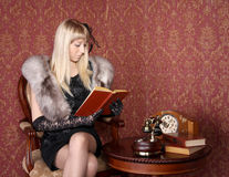 Retro woman reading book near table Royalty Free Stock Photography