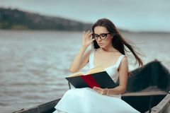 Retro Woman Reading a Book in a Vintage Boat. Beautiful girl reading a novel in an old fisherman boat Stock Photo