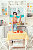 Retro woman with a rolling pin. Pin-up girl style. Retro girl standing in the kitchen with a rolling pin for the dough in his hands Stock Images