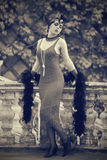 Retro Woman 1920s - 1930s. Toned Full Length Portrait of The Beautiful Retro woman in Dress and Accessories in Style 1920s - 1930s Standing at the Old Terrace Royalty Free Stock Images