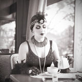 Retro Woman 1920 - 1930 Sitting in a Restaurant. Retro Charleston Woman Fashion of 1920 - 1930 Sitting in a Restaurant Holding a Cup of Tea. Black and White Royalty Free Stock Image