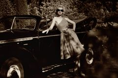 Retro woman standing near convertible Royalty Free Stock Photo