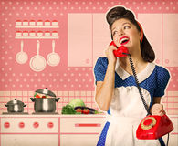 Retro woman talking on phone in her kitchen interior poster Royalty Free Stock Image