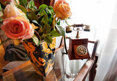 Retro wood telephone and vase full of roses Stock Image