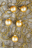 On retro wooden background gold christmas balls and beads Stock Images