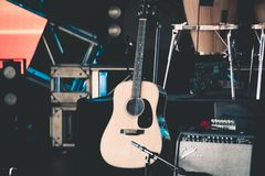Retro wooden guitar on stage with some concert stuff royalty free stock photography