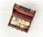 Retro wooden money chest filled with coins Stock Photo