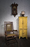 Retro wooden rocking chair, yellow cupboard and pendulum clock Stock Image