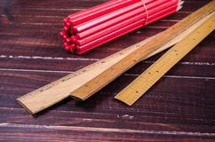 Retro wooden ruler and red wooden pencil on wooden board Stock Photography