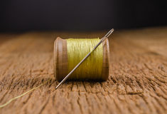 Retro wooden spool thread with needle. Vintage wooden spool thread with needle on wooden board Royalty Free Stock Images