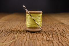 Retro wooden spool thread with needle. Vintage wooden spool thread with needle on wooden board Stock Images