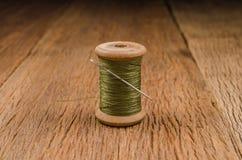 Retro wooden spool thread with needle. Vintage wooden spool thread with needle on wooden board Stock Image