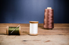Retro wooden spool thread with needle. Vintage wooden spool thread with needle on wooden board Stock Photo