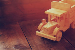 Retro wooden toy car over wooden table. room for text. nostalgia and simplicity concept. retro style image.  Stock Photo