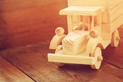 Retro wooden toy car over wooden table. room for text. nostalgia and simplicity concept. retro style image.  Royalty Free Stock Photos