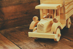 Retro wooden toy car over wooden table. room for text. nostalgia and simplicity concept. retro style image.  Stock Images