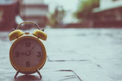 Retro yellow alarm clock with Nine Five Minutes Old Style, in rainy season,On road Vintage stock image
